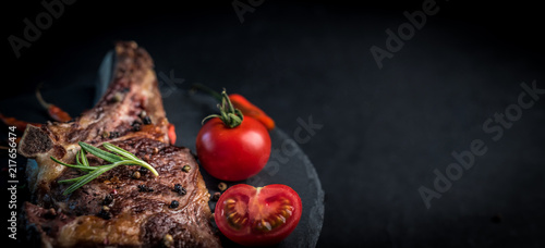 Valokuva  Close-up of grilled beef steak on bone with tomatoes on the stone cutting board