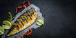 Grilled mackerel fish with lime on a black background, copy space fried fish and vegetables