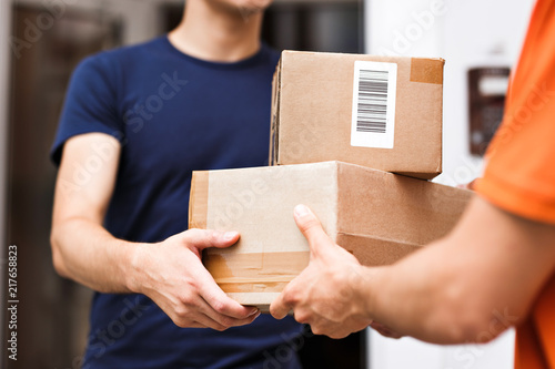 Fotografía  A person wearing an orange T-shirt is delivering parcels to a satisfied client