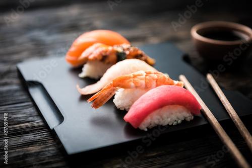 Poster Sushi bar close up of sashimi sushi set with chopsticks and soy on black background