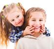 Little girl using her fingers to make her older sister smile isolated on white background