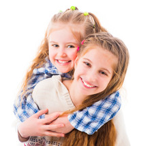 Portrait Of Two Joyful Beautiful Sisters Embracing Warmly Isolated On White Background