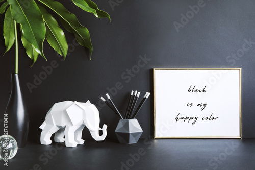 Photo  Black design room with mock up photo frame, elephant figures, tropical leaf and office accessories