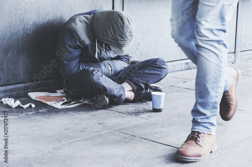 Fotografie, Obraz Homeless man sitting on the street in the shadow of the building and begging for help and money