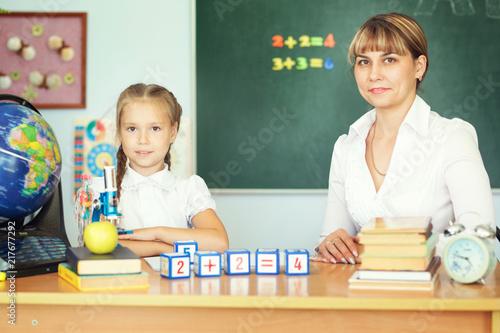 Teacher Helping Schoolgirl With Her Homework In Classroom At School