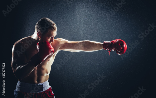 Photo  Boxer striking a blow in the rain.