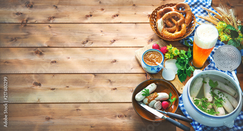 Tableau sur Toile Bavarian sausages with pretzels, sweet mustard and beer on rustic wooden table