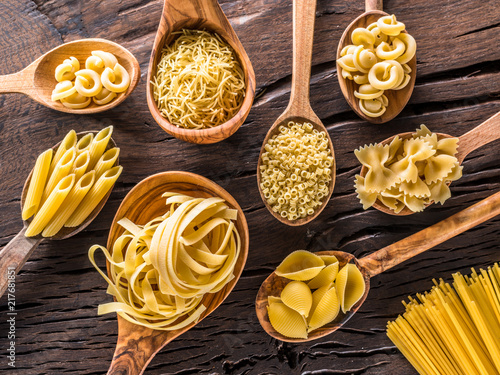 Different pasta types in wooden spoons on the table. Top view.