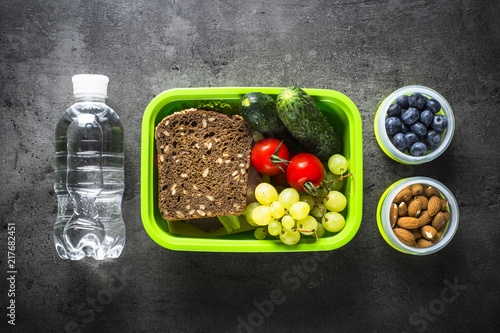 Papiers peints Assortiment Lunch box with sandwich, vegetables, banana, water, nuts and ber