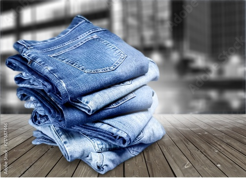Fotografia  Pile of blue jeans over white background