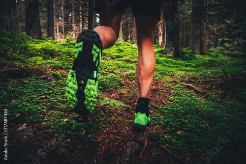 Trail shoes man running on trail through green forest