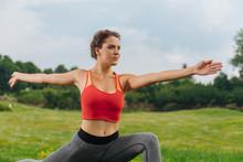 Boosting Energy. Sportswoman Wearing Grey Leggings Boosting Her Energy While Doing Morning Exercise