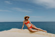 Young woman in straw hat and red bikini lying on the stone edge with beautiful view on ocean. Summer vocation