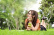 canvas print picture - Happy Asian woman resting and looking beside in park with smartphone. People nad lifestyles concept. Technology and Beauty theme.