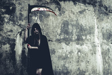 Demon Witch With Reaper Standing In Front Of Grunge Wall Background. Halloween And Religious Concept. Demon Angel And Satan Theme.