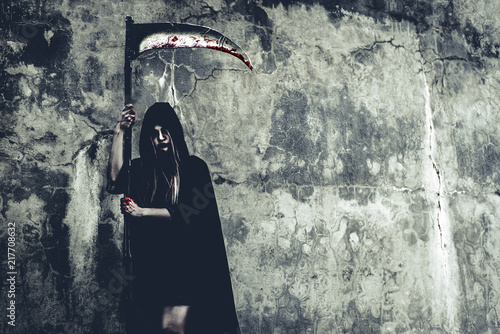 Cuadros en Lienzo Demon witch with reaper standing in front of grunge wall background