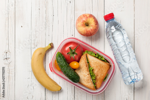 Papiers peints Assortiment Lunch box with sandwich and tomatoes, water bottle, apple, banana