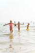 Children playing in sea water with wide spread hands