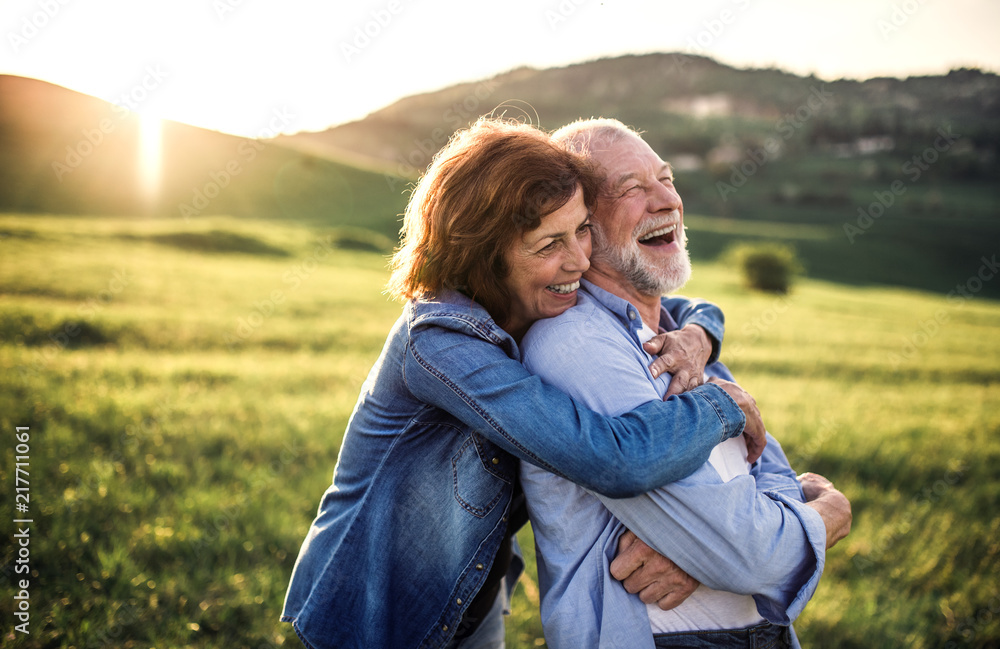 Fototapeta Side view of senior couple hugging outside in spring nature at sunset.
