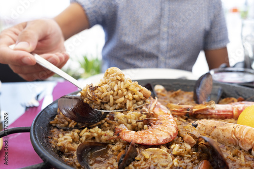 man serving a typical spanish seafood paella