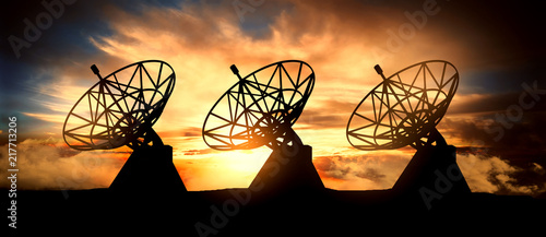 Photo  Three satelite dishes over sunset