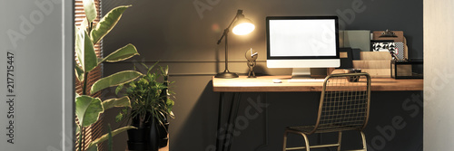 Creative golden, metal chair by a wooden desk with computer screen, folders and Canvas Print