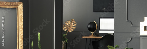 Fotografie, Obraz  Golden decorations in a chic living room interior with gray walls and a computer
