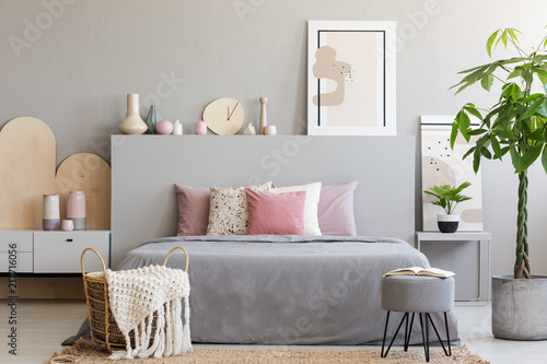 Fototapety, obrazy: Basket with blanket and stool in front of bed in grey bedroom interior with palm and poster. Real photo