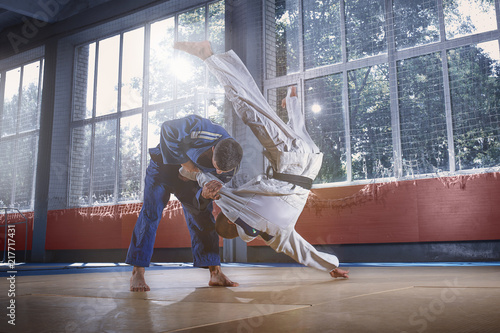 Two judo fighters showing technical skill while practicing martial arts in a fight club Canvas Print