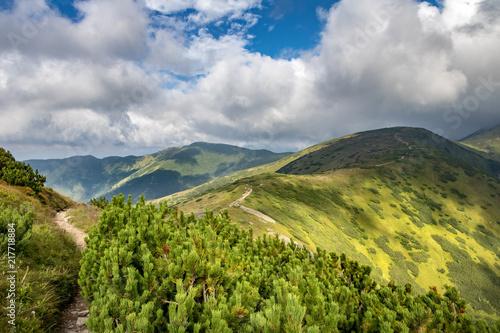 Tela Path through summer mountain ridge under cloudy sky