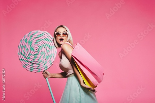 Fotografia Model posing with with sweets and shopping bags