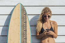 Woman Surfer Typing On Cell Phone