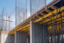 Reinforced Concrete Structures Of The Building Under Construction. Scaffolding And Support. Construction Crane
