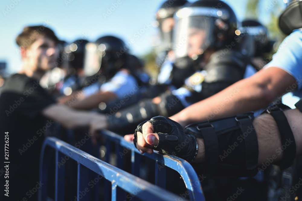 Fototapety, obrazy:  Security staff hands on a protection fence during a riot