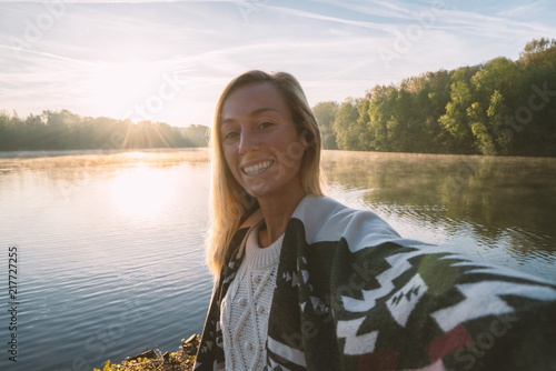Photo  Young woman by the lake at sunrise takes a selfie portrait using mobile phone, beautiful reflection on water surface, model wearing blanket