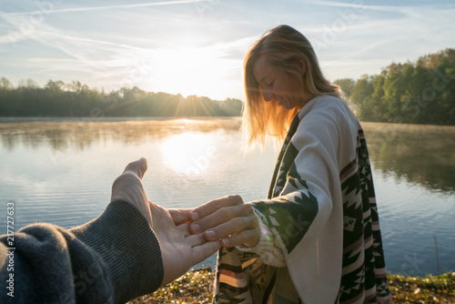 Photo  Follow me to concept, Young woman leading boyfriend to the lakeshore at sunrise, holding hands, People travel couple beginning