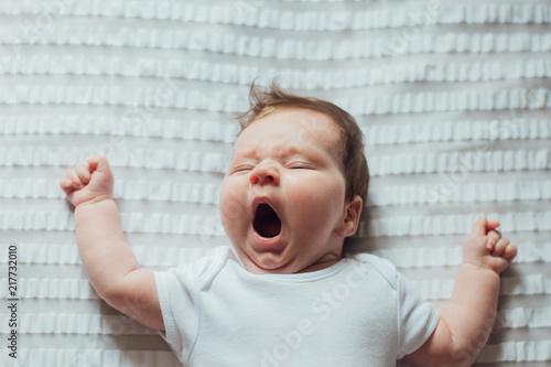 Obraz Infant baby sleeping and yawning on white sheets - fototapety do salonu