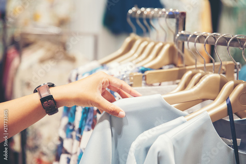Obraz hand of customer choosing clothes in a clothing store - fototapety do salonu