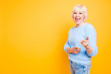 Portrait Of Confident Modern Granny Pointing Two Index Fingers A