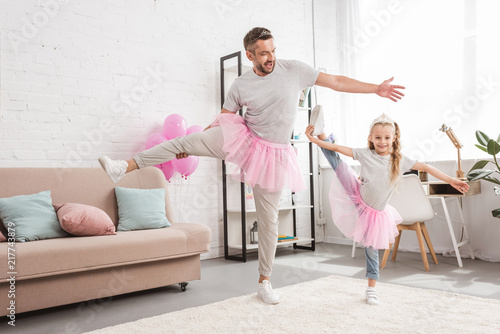 Carta da parati front view of father and daughter in tutu skirts standing on one leg