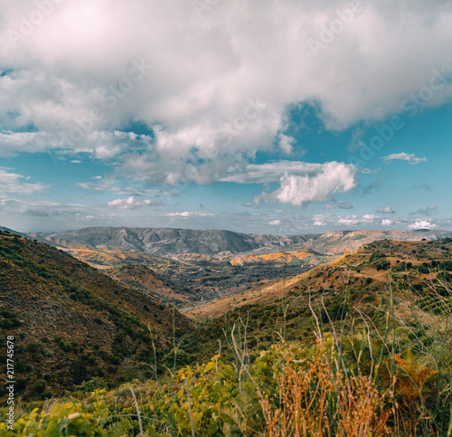 Crete Greece, View on mountains with low hanging clouds and blue sky and green trees. South Crete neat Rethymno, Greece