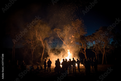 A large group of people gathering around a bonfire Fototapet
