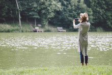 Rear View Of Woman Photographing With Mobile Phone While Standing At Lakeshore In Forest