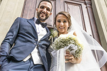 Low Angle Portrait Of Happy Newlywed Couple Standing At Church Entrance