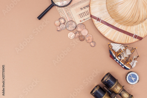 Fototapeta top view on items for travel, recreation and adventure: map, binoculars, straw hat, vintage paper and coins, magnifying glass, watch, compass, ship on beige background as a frame. flat lay obraz na płótnie