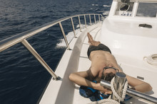 High Angle View Of Man Lying On Yacht In Sea