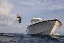 Low Angle View Of Man Diving Into Sea From Yacht Against Cloudy Sky At Maldives