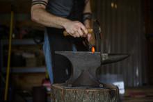 Midsection Of Blacksmith Forging Knife On Anvil In Workshop