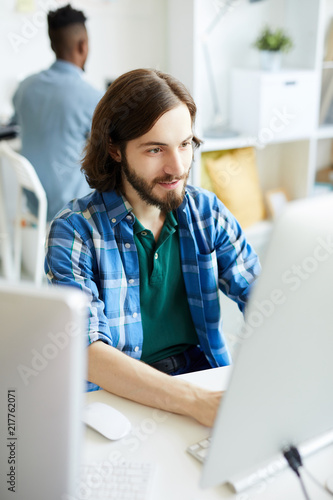 Cuadros en Lienzo Young bearded man in casualwear sitting in front of computer monitor and carryin