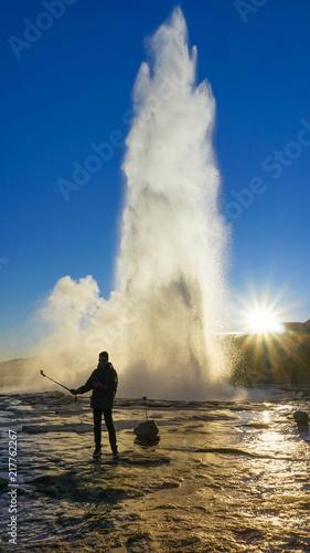 Slika na platnu Male tourist took photo himself in between Geysir hot spring eruption